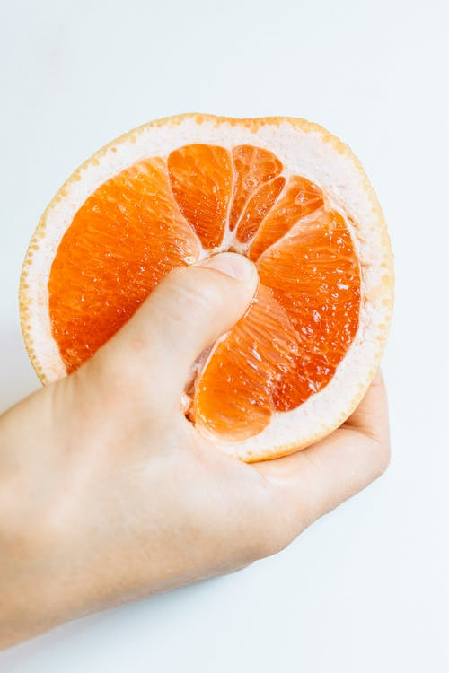 Persona Sosteniendo Rodajas De Naranja