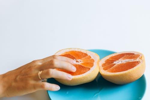 Person Touching Sliced Orange Fruit