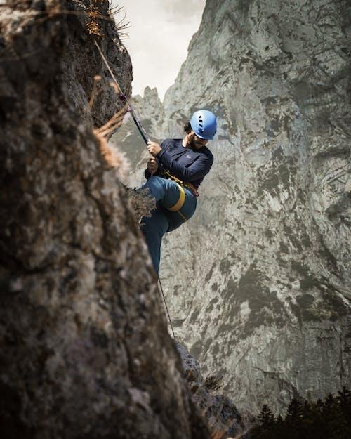 Man in Blue Jacket Climbing on Brown Rock