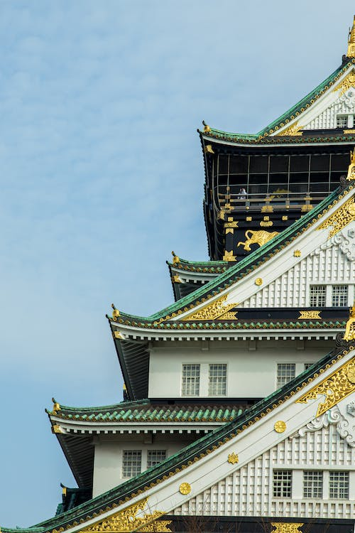 Facade of authentic ancient Osaka Castle with typical roofs and golden decorative details located beneath clear blue sky