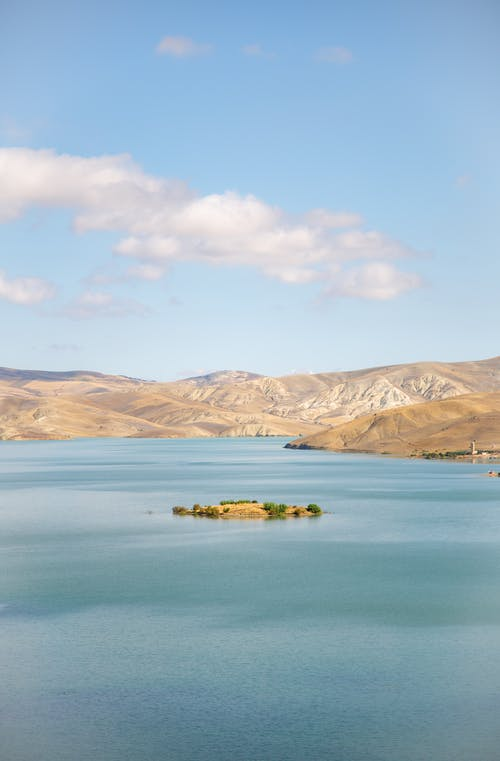 Picturesque scenery of tranquil blue lake located on hilly terrain on fair weather