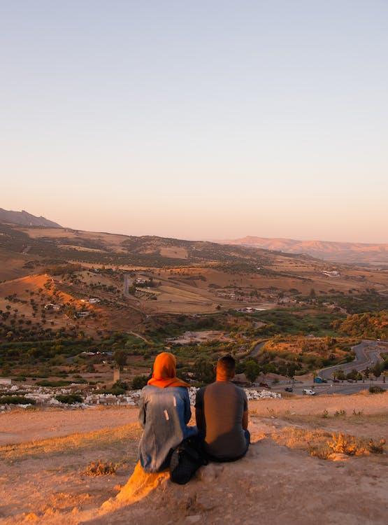 언덕이 많은 계곡에 농촌 정착촌을 통해 일몰을 즐기는 인식 할 수없는 부부