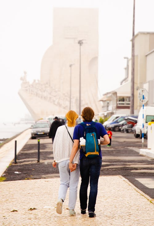Faceless romantic couple walking together on city harbor