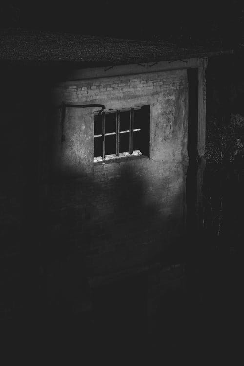 Black and white of old shabby house with small window with grid in countryside at night