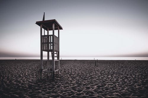 Lifeguard tower on empty sandy seashore at sundown