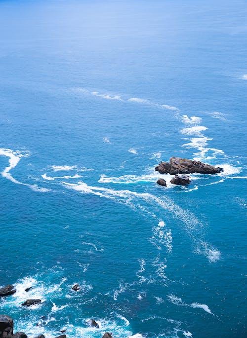 Shallow blue sea washing rough rocks