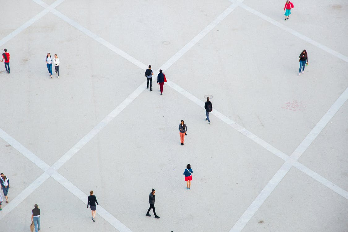 High angle citizens in casual wear walking on vast concrete ground in city square