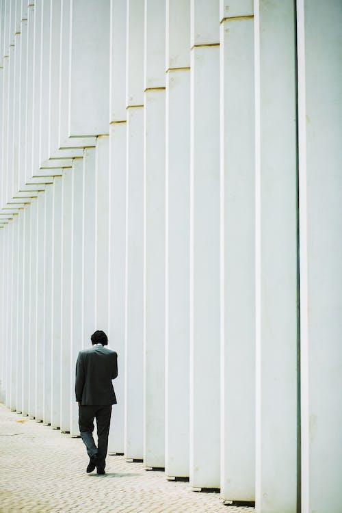 Homme Méconnaissable Marchant Le Long Du Mur Du Bâtiment Blanc