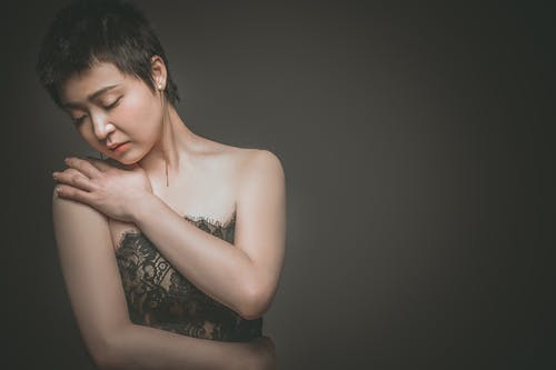 Crop dreamy Asian woman in trendy outfit on gray background