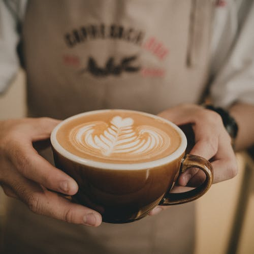 Barista holding cup of latte with art