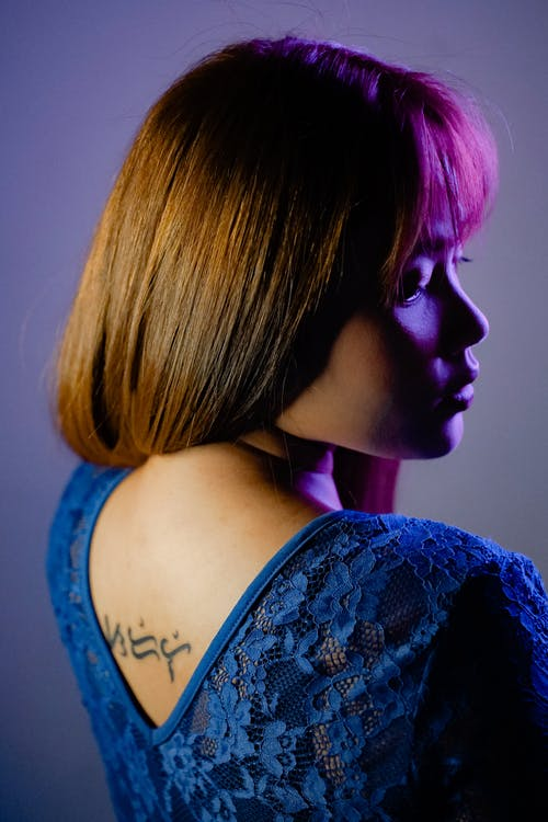Side view of attractive female profile wearing blue blouse with hieroglyphs on back standing in studio under neon light against wall