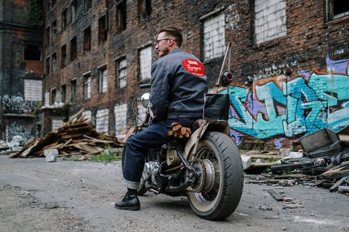 Man in Blue Jacket and Blue Denim Jeans Riding Black Motorcycle
