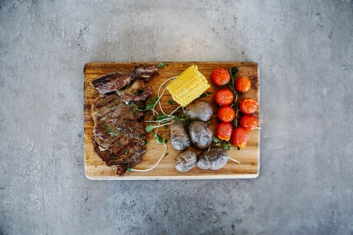 Grilled Meat with Vegetables on Wooden Chopping Board