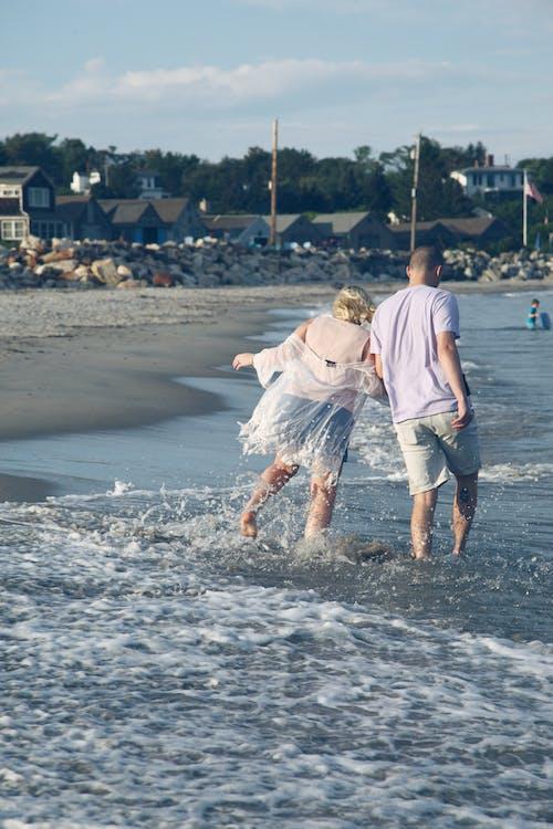 Man in White T-shirt and Blue Denim Shorts Walking on Beach