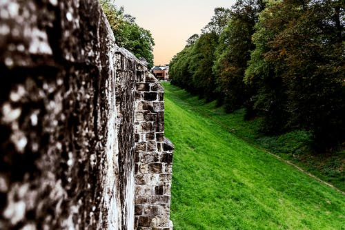 Free stock photo of buildings, moat, rock wall