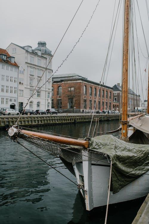 Barco Branco E Marrom Na água Perto De Edifícios