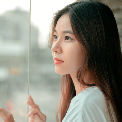 Young dreamy Asian female with long brown hair standing near glass wall and looking away in daytime