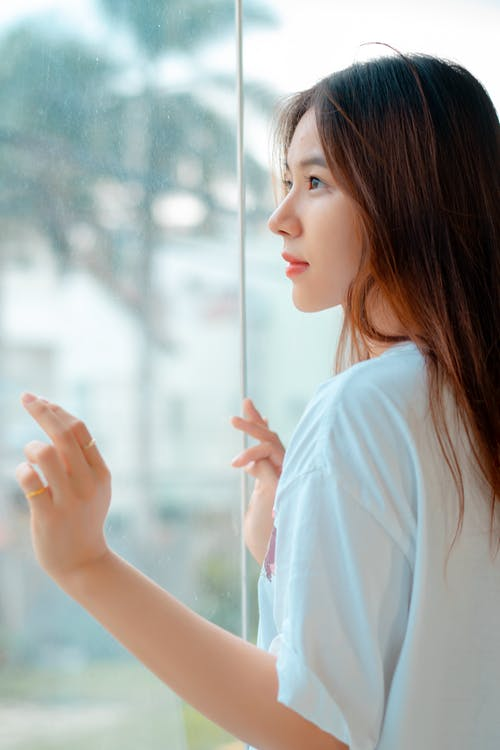 Charming young Asian female with long brown hair in white t shirt standing near glass wall in daytime