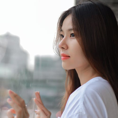 Pensive Asian female with brown hair standing near window and touching glass in daytime