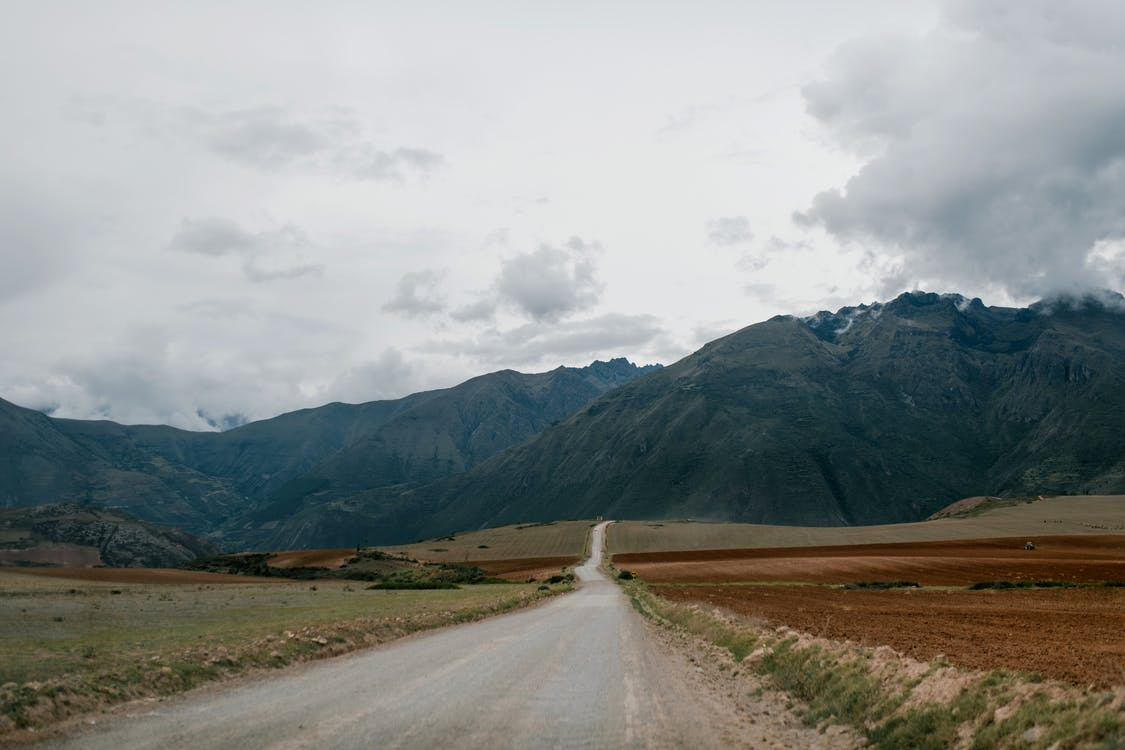 Empty road leading towards high mountains with clouds above
