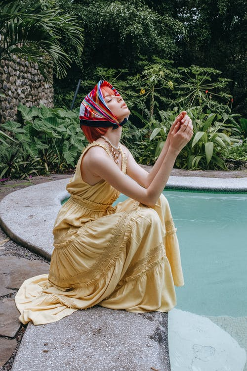 Side view full length charming young female in yellow maxi dress and silk headscarf sitting near swimming pool in tropical resort