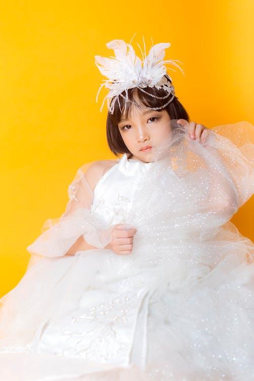 Ragazza In Vestito Bianco Con La Fascia Del Fiore Bianco