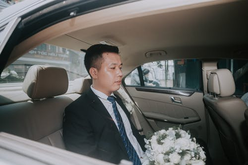 Side view of serious Asian man in elegant suit sitting in expensive automobile with wedding bouquet in hands in daytime