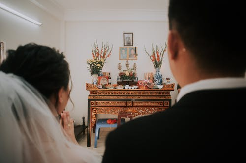 Back view of blurred groom and bride against ornamental shrine during ceremony of marriage