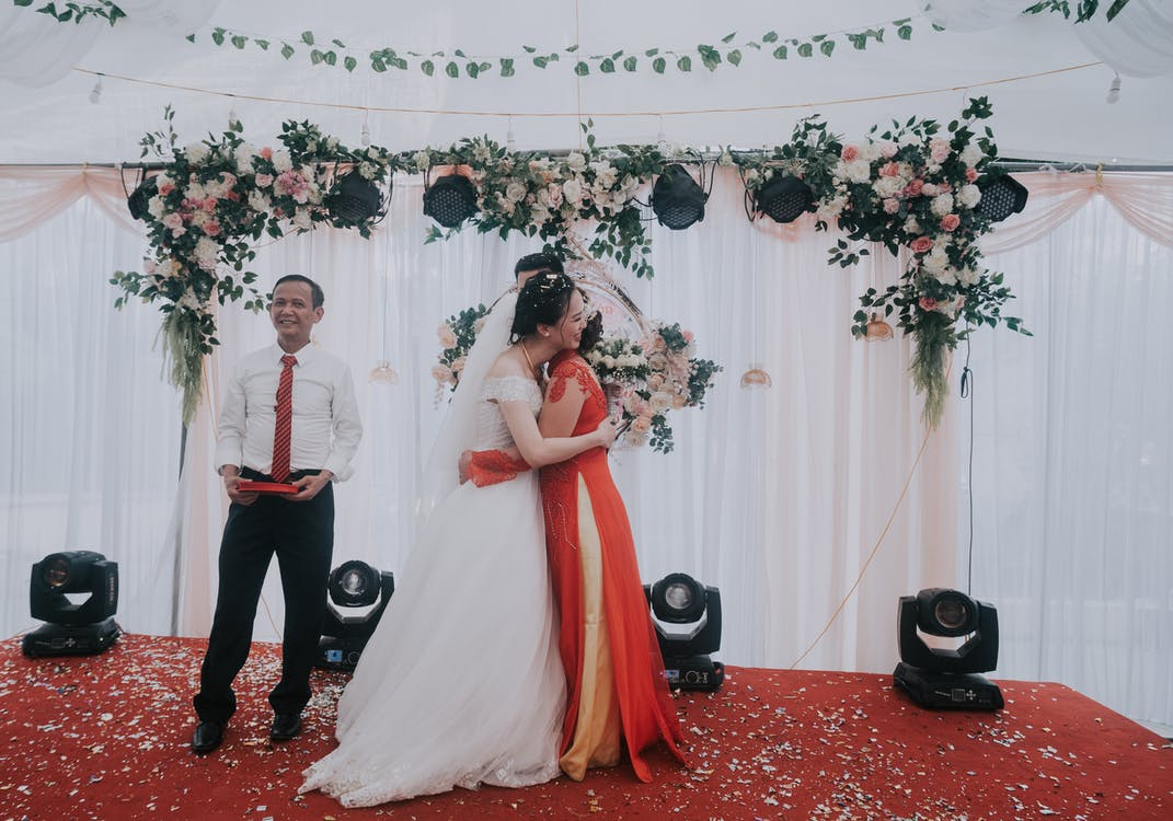 Full body of loving Asian family celebrating wedding of young couple in festive tent