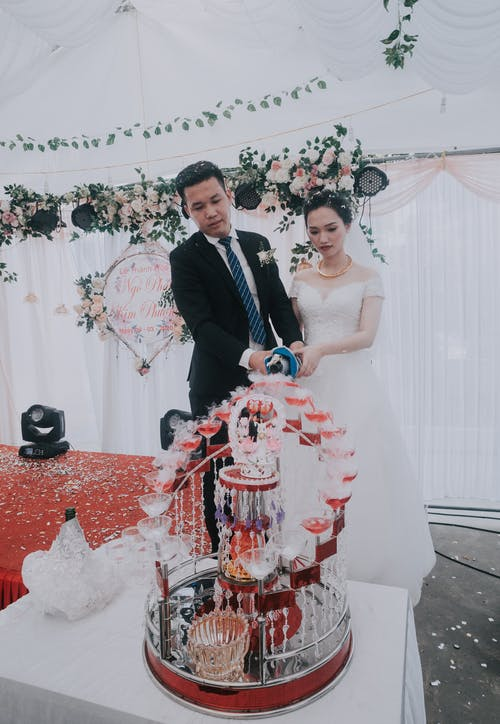 Young Asian bride and groom pouring champagne into glasses composed in tower on wedding festive dinner