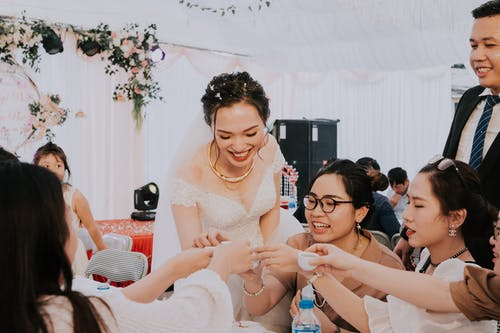 Happy newlyweds toasting with guests