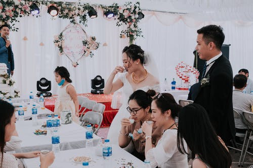 Young ethnic bride with groom and guests in elegant tent drinking together while toasting