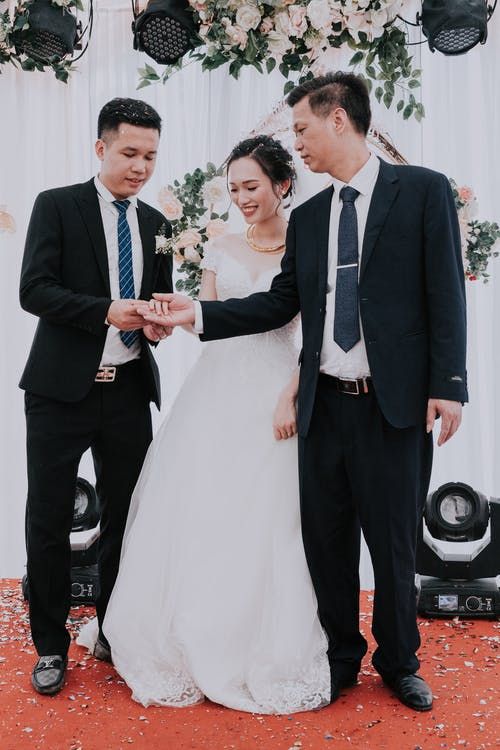 Full body young Asian couple with best man holding hands while having wedding ceremony