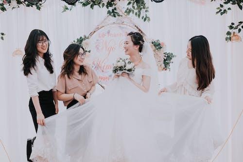 Happy ethnic bride and bridesmaids in wedding tent