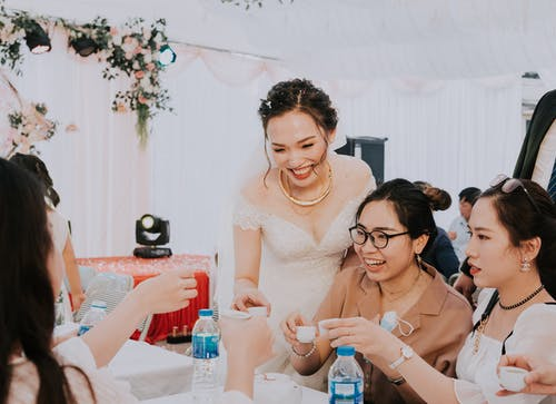 Happy bride with girlfriends clinking with alcohol