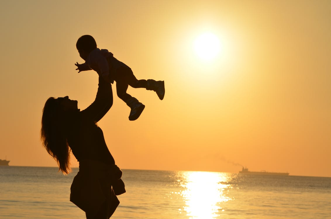 Woman Carrying Baby at Beach during Sunset
