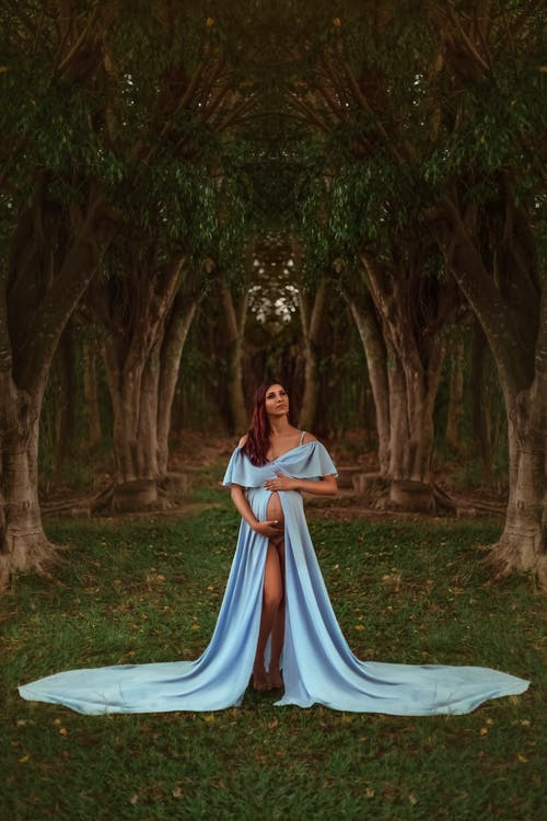 Woman in White and Blue Dress Sitting on Green Grass Field Surrounded by Trees