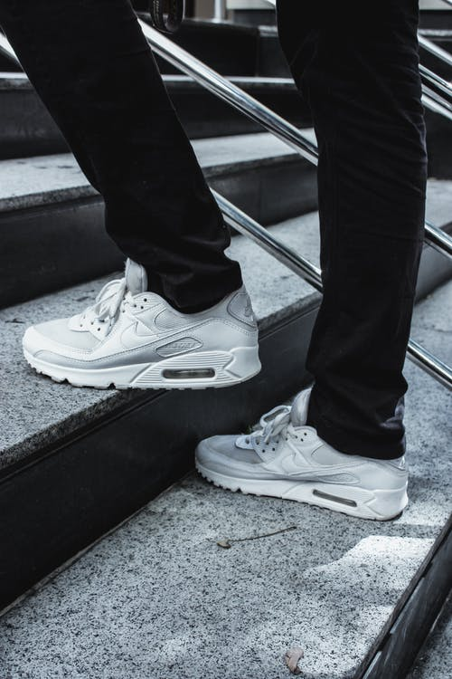 Person Wearing White Nike Sneakers Walking on Stairs