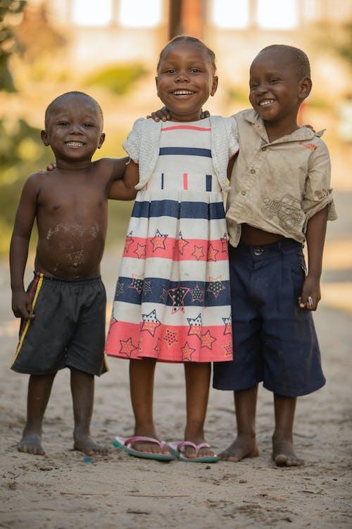 Smiling black children standing on street