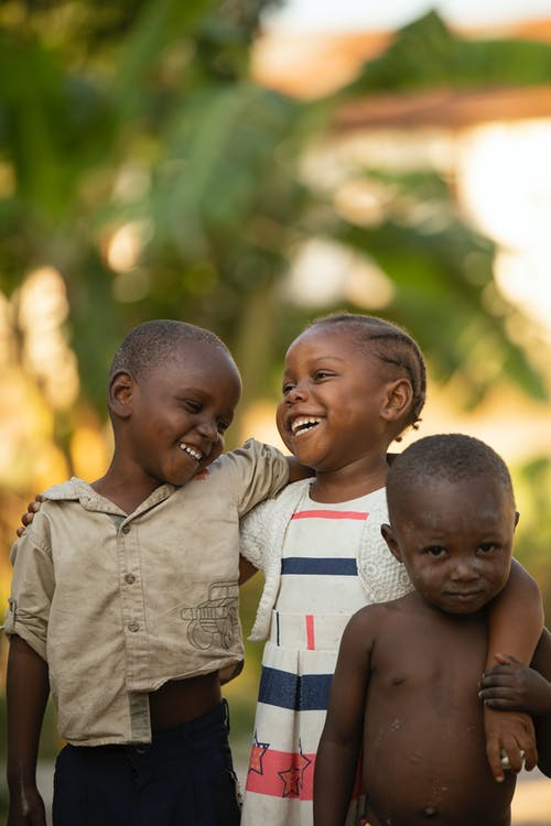 Laughing local African boys and girl in weathered clothes hugging and standing on street in sunny day