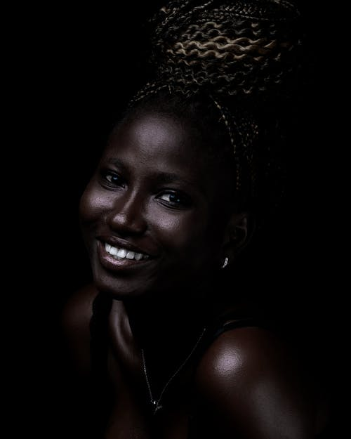 High angle of cheerful African female with toothy smile and brown eyes looking at camera