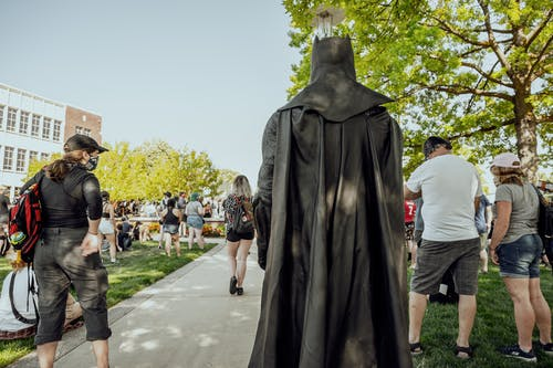 Anonymous person in superhero costume walking in park
