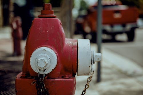 Shabby red and white metal fire hydrant with rusty chain located on city street in daytime