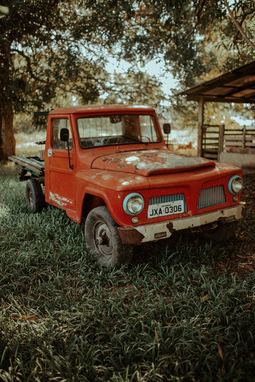 Red Single Cab Pickup Truck Parked on Green Grass Field