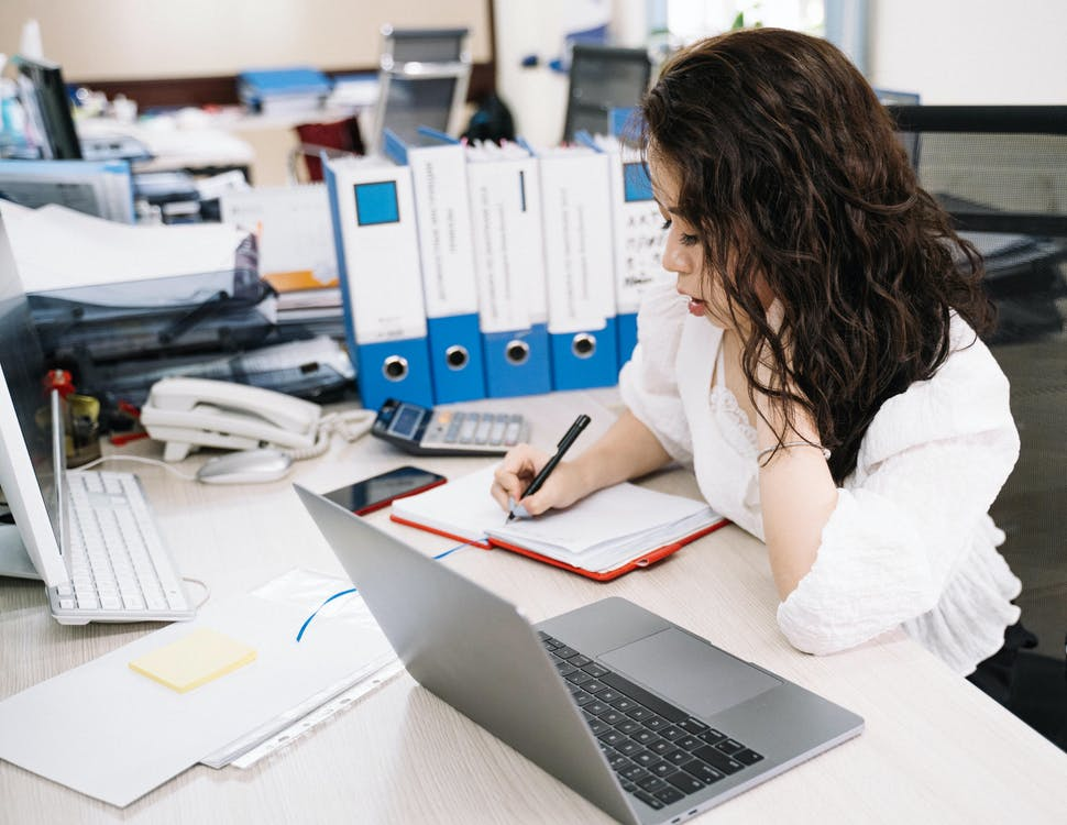 Woman Writing on Notebook While Using Laptop