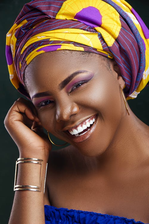 Cheerful African woman with colorful makeup in bright trendy turban touching face and looking at camera