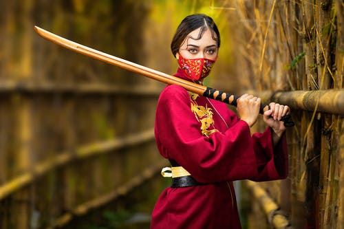 Unrecognizable woman in samurai costume with shinai