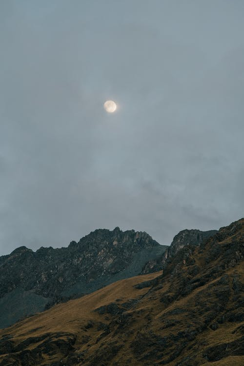 Mountain Peaks Under a Moon During Dawn
