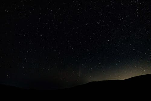 Stars glowing in night sky over mountains