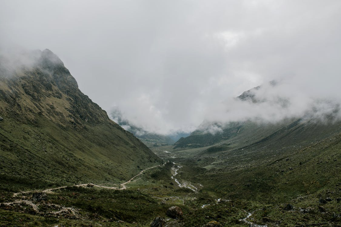 Wide valley surrounded by mountains and branching river under clouds